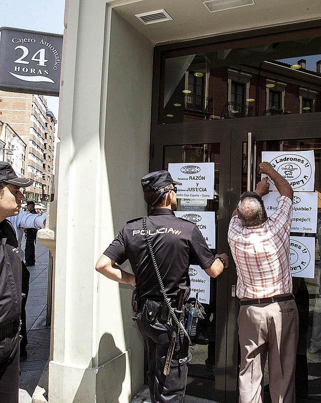 Imagen de un manifestante colocando un cartel en una de las sedes. ÓSCAR NAVARRO