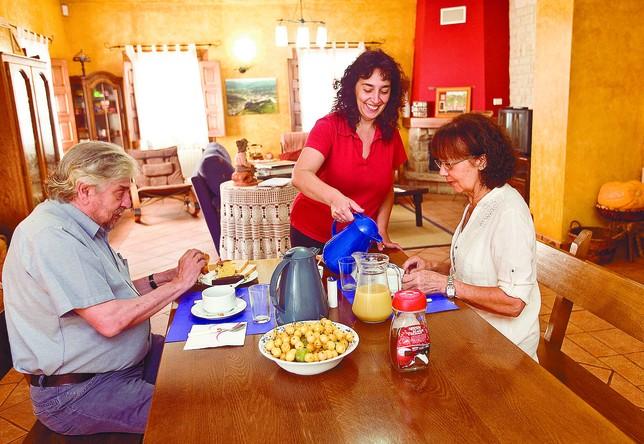 Virginia, propietaria de la casa rural El Cauce (San Medel), sirve el desayuno a dos clientes que han estado alojados este puente. Jesús J. Matías