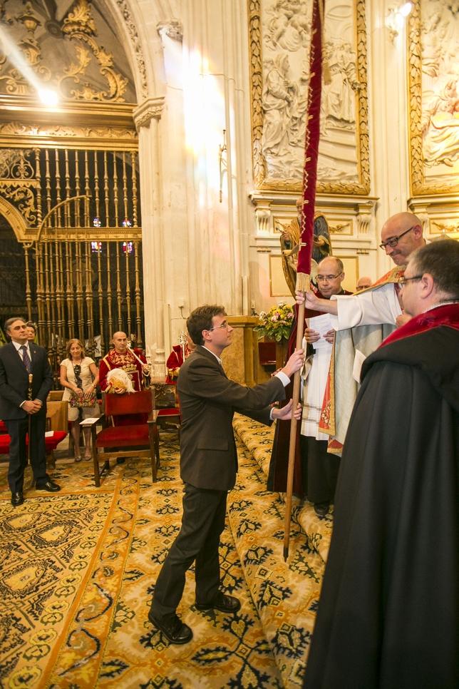 El capellán mayor, Miguel Ángel Albares, entrega al edil más joven, Pablo García (IU), el pendón de Alfonso VIII.  Reyes Martínez