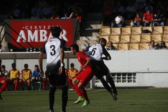 Carlos Álvarez salta en pugna por un balón aéreo con Lázaro. Valdivielso