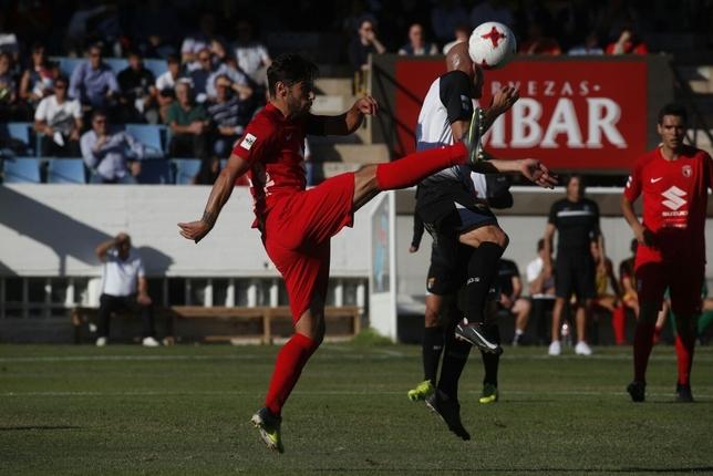 Andrés intenta despejar un balón en un salto con un rival. Valdivielso