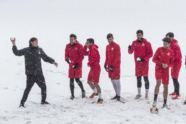 Patxi Salinas y sus futbolistas disfrutaron en el entrenamiento de ayer con la nieve caída sobre la capital burgalesa que cubrió con un manto blanco el césped del estadio municipal. Alberto Rodrigo
