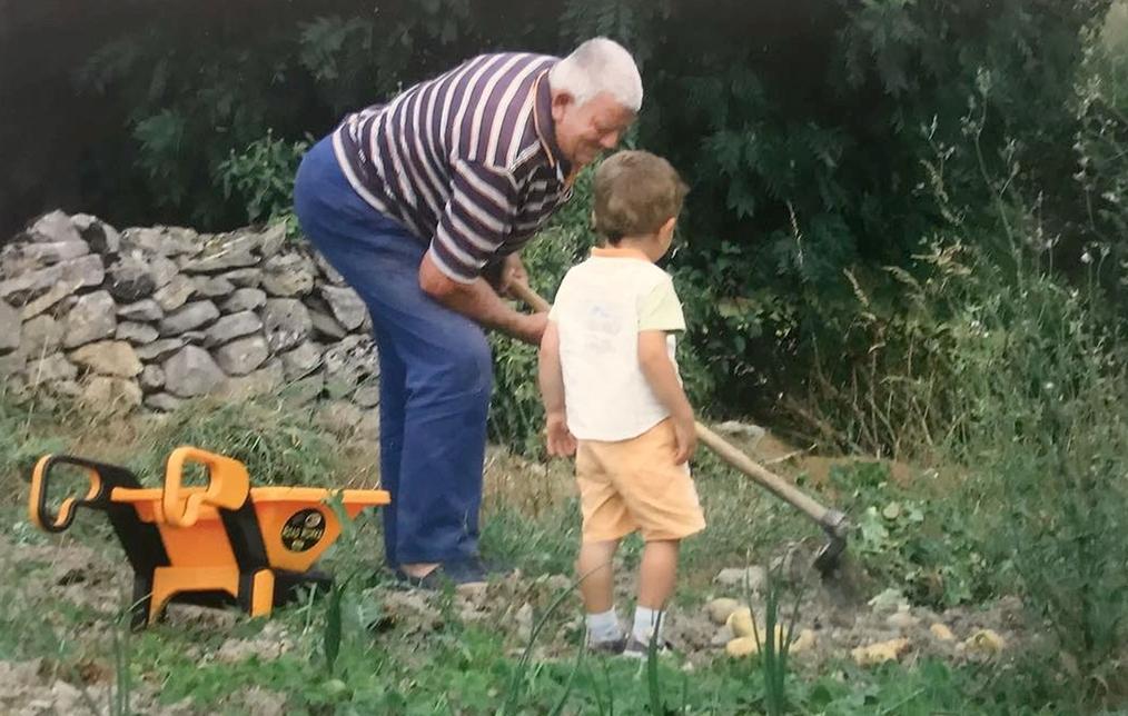 Jesús saca patatas de su huerto con un nieto. DB