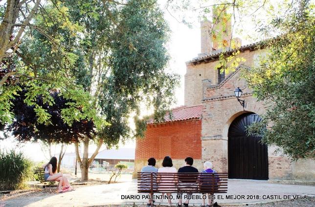 Las distintas generaciones de vecinas disfrutan de la sombra junto a la iglesia, pero reservándose los espacios por edades para conversar y pasar el rato.