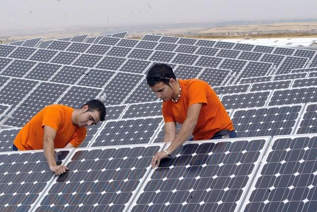 Una pareja de operarios termina de instalar un panel solar en un parque de reciente desarrollo.