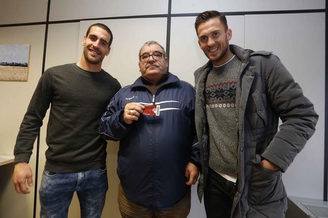 Los jugadores del Alba Carlos Delgado y Álvaro Arroyo entregan los abonos a los afortunados
