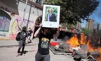 En mitad de los disturbios, un hombre sujeta una foto del presidente de Chile, Sebastián Piñera