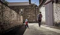 Una madre y su hijo transitan por una calle de un municipio pequeño, en una imagen de archivo.