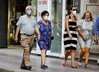 Un grupo de personas caminan por la calle con la mascarilla puesta.
