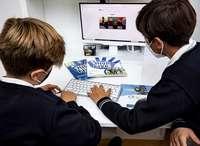 Dos niños realizan unos deberes de inglés en un ordenador de sobremesa.