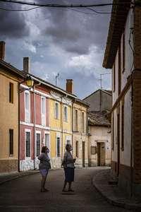 Dos vecinas de un pueblo vallisoletano pasean por unas calles cada vez más vacías.