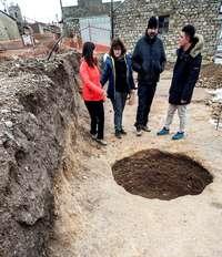 El equipo de arqueólogos y el alcalde contemplan unos silos que salieron a la luz el año pasado al hacer las obras de la plaza.