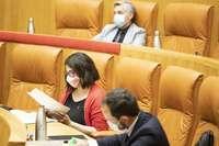 La diputada de Podemos, Raquel Romero, en su escaño del Parlamento. Arriba, Francisco Ocón, del PSOE.