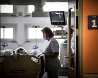 Imagen de una sanitaria con una paciente en una UCI