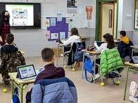 Imagen del interior de un aula con varios dispositivos móviles conectados.