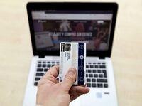 Un hombre sostiene una tarjeta para realizar una compra online.
