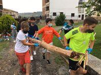 Un grupo de chavales retira restos de ramas y troncos arrastrados por la riada.