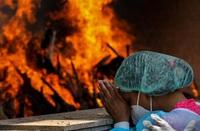 Una mujer reza en un crematorio este viernes en Nueva Delhi