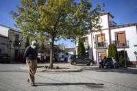 Un vecino de Robledo pasea por la plaza del municipio, con el Ayuntamiento al fondo.