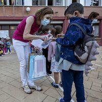 Una docente echa gel a un alumno antes de entrar a un colegio público de Burgos.