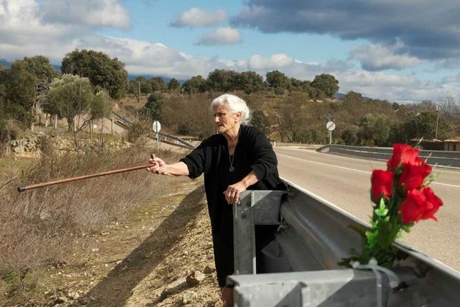 María Martín muestra el lugar donde dice que está enterrada su madre. En primer plano, un ramo de flores colocado por la octogenaria. Chinarro y Mimoso