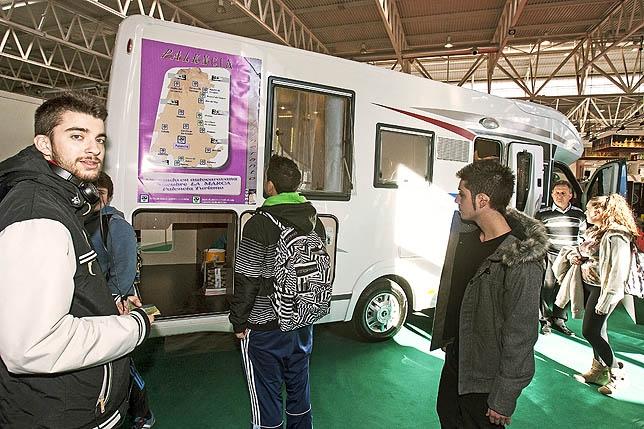 Varios jóvenes óbservan en 'Intur' el mapa de áreas de autocaravanas de la provincia.