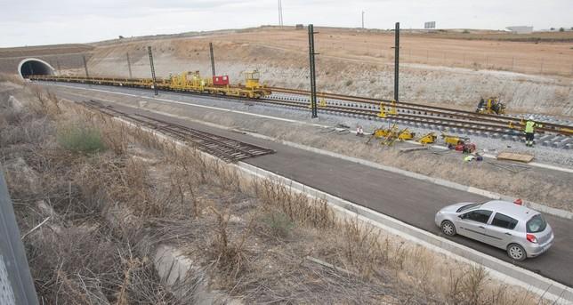 Operarios de 'Ferrovial' supervisan el deslizamiento de los raíles desde el tren carrilero hasta las traviesas, donde los rodillos ayudan al arrastre del acero. De las vías tira una máquina a un kilómetro de distancia.  Eva Garrido