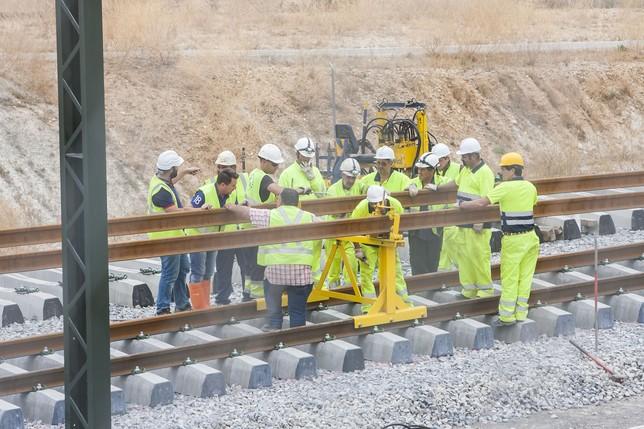 Operarios de 'Ferrovial' supervisan el deslizamiento de los raíles desde el tren carrilero hasta las traviesas, donde los rodillos ayudan al arrastre del acero. De las vías tira una máquina a un kilómetro de distancia.