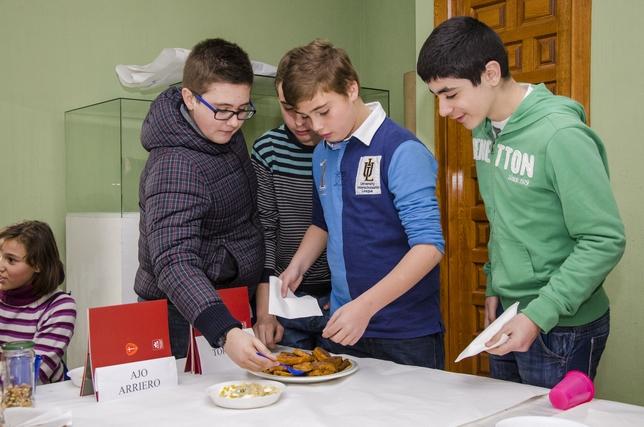 Un grupo de jóvenes nazarenos degusta las torrijas y el ajoarriero.