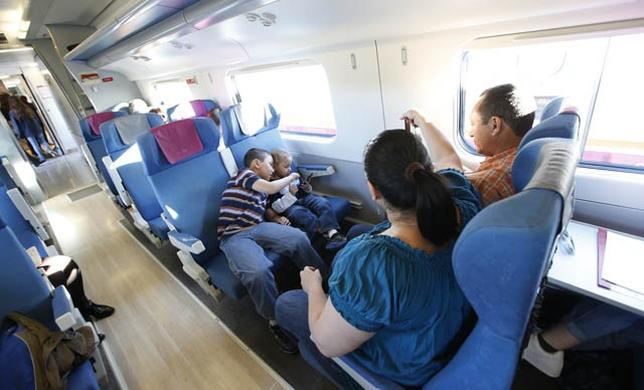 Los pequeños Douglas y Diego, junto a sus padres en el trayecto de vuelta a Madrid tras pasar el día en Toledo./ yolanda lancha