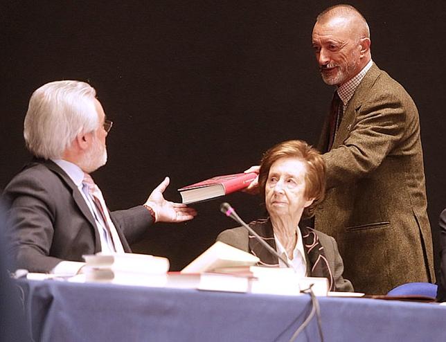 Arturo Pérez-Reverte entrega a Darío Villanueva una copia de su último libro./