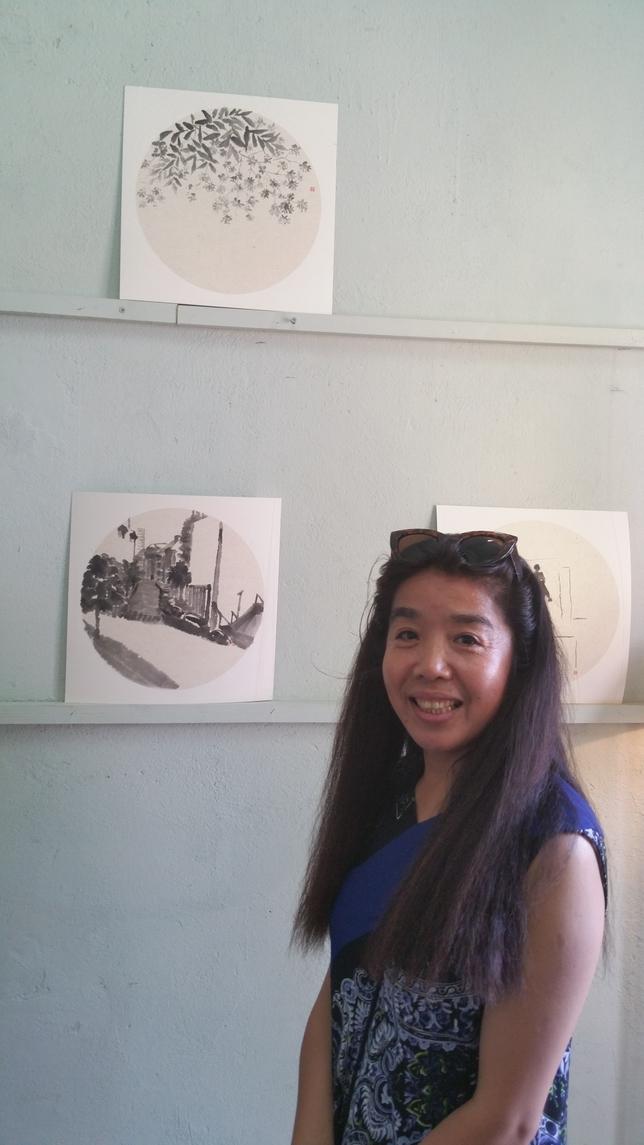 La profesora Zhan Ping junto a dos de las pinturas de su exposición.  Eduardo Gutiérrez