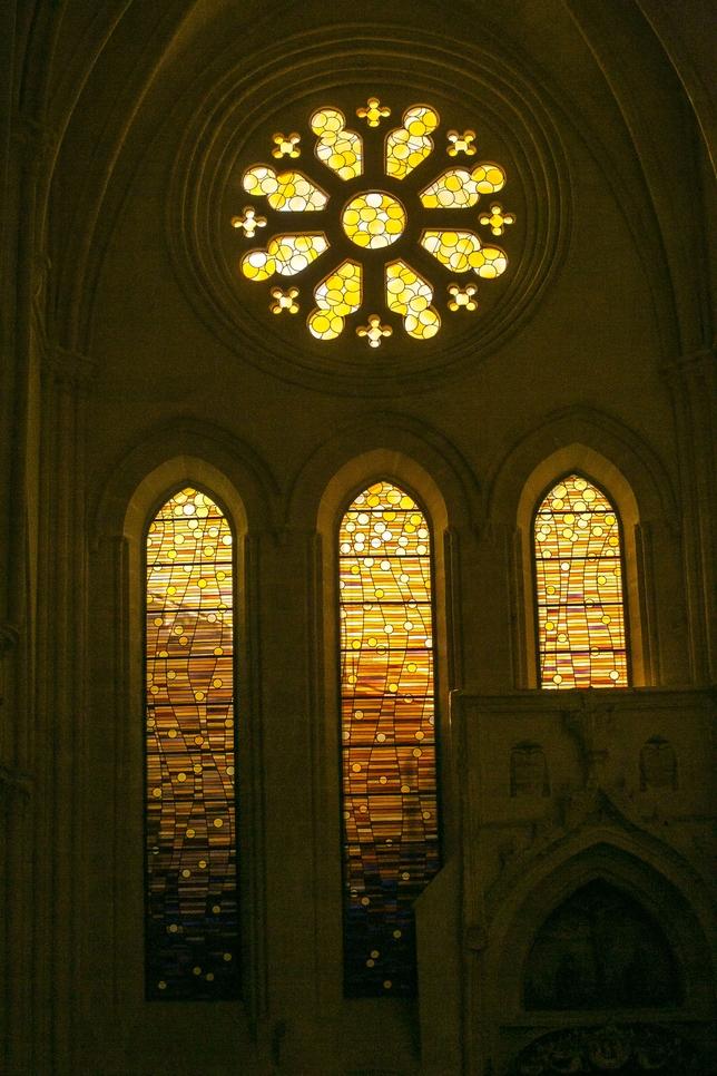 Tres de las vidrieras y el rosetón diseñados por Torner para la nave derecha de la catedral. El rosetón simboliza a Jesucristo, y los círculos ascendentes, La Creación, entendida como obra que retorna a Dios.