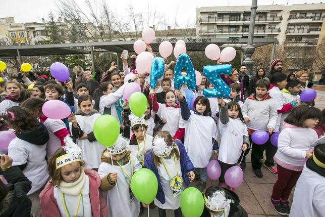 Estudiantes de Primaria sostienen unos globos en los que se puede leer la palabra 'paz'.