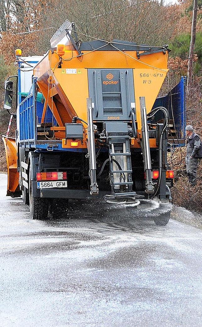 Una quitanieves esparce sal por la carretera.