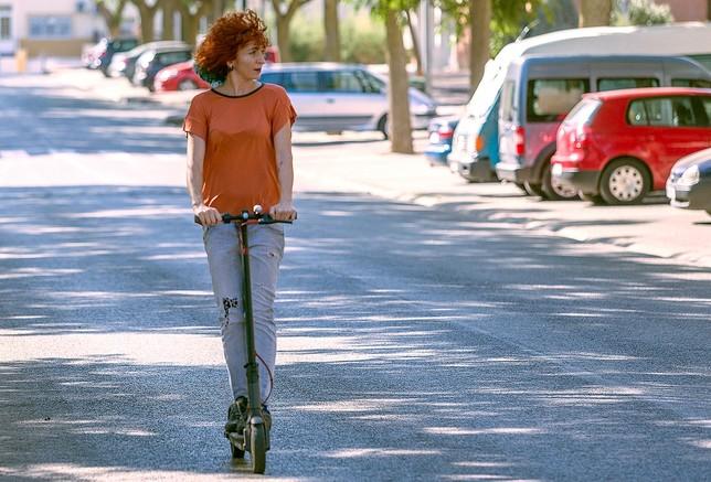 Una mujer hace uso de un patinete.