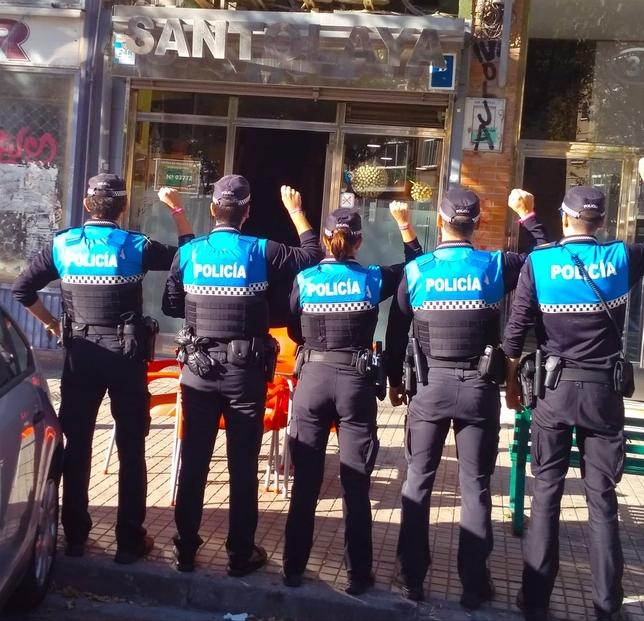 Un grupo de policías locales de Burgos con las pulseras solidarias en el bar Santolaya de Casa la Vega, que se ha establecido como punto de acogida para los corredores en la capital. DB