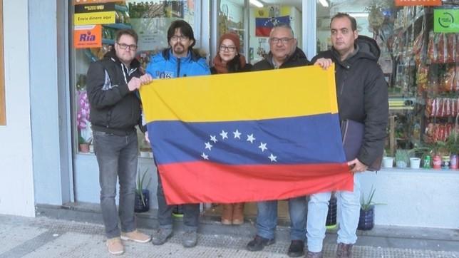 Grupo de venezolanos residentes en Navarra sujetan la bandera de su país