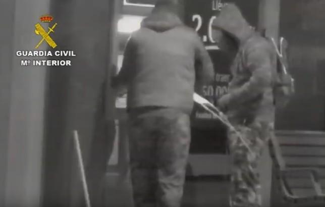 Los delincuentes, colocando un explosivo en un cajero.