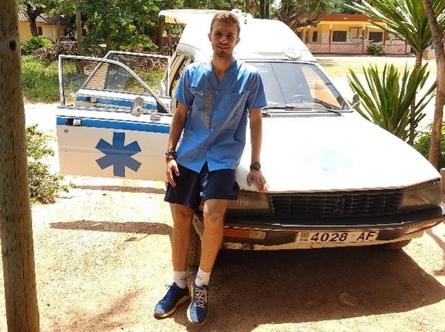 El egresado de la UCLM apoyado en uno de los vehículos sanitarios de Togo.
