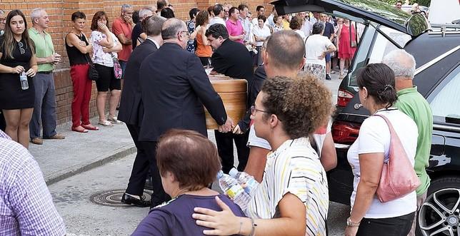 Varios hombres portan unos de los féretros a la salida de la ceremonia, ante la atenta mirada de vecinos y amigos