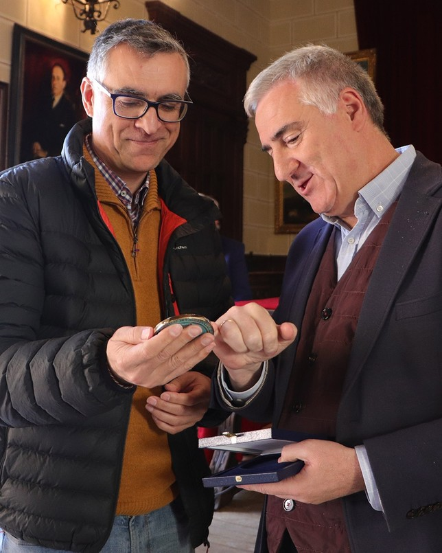 El ministro provincial Pedro Huertas observa los detalles de la medalla de la ciudad recibida. LT