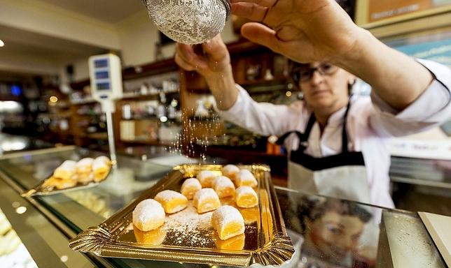 Milagros García glasea en la pastelería Silma las yemas de Burgos antes expedirlas al cliente. Valdivielso