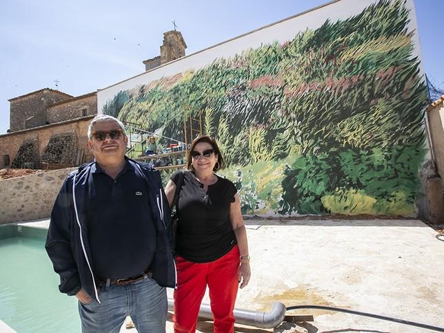 Sagrario y Fernando, un matrimonio que reside en Madrid, muestran el mural de la nueva casa que han comprado en la localidad.