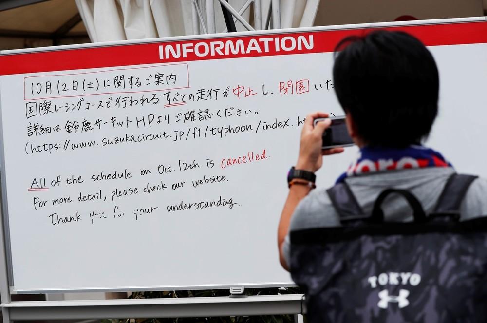 Un aficionado fotografía un cartel donde se informa de la suspensión de los entrenamientos del sábado