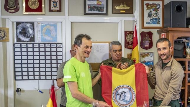 El ministro y el comandante Juan José Pereda (d.), con la bandera española y el logotipo de la Misión Antártica del Ejército de Tierra.