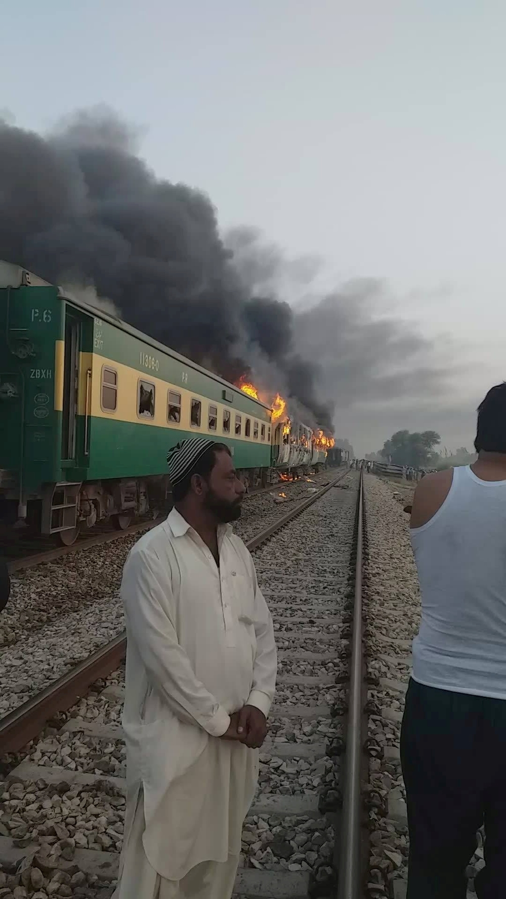 A man stands in front of a burning train after a gas canister passengers were using to cook breakfast exploded, near the town of Rahim Yar Khan
