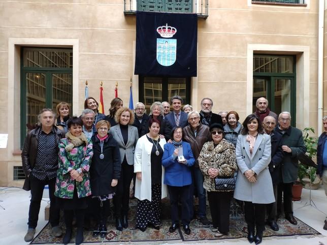 Miembros de la corporación, la Sociedad Filarmónica y autoridades posan tras el acto de entrega de la Medalla