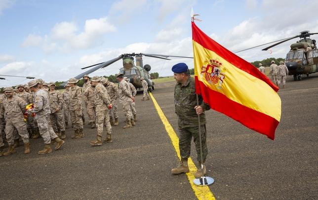 Un boina azul del BHELA I sostiene la bandera de España en la pista de la base de Almagro