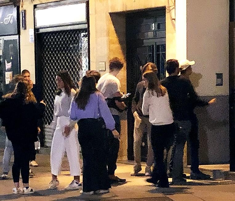 Estudiantes universitarios, en la Calle Real, a la espera de acceder a un piso donde se celebra una fiesta.